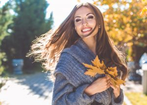 Happy girl is wearing warm knitted gray coat in park with maple yellow leaves, autumn time